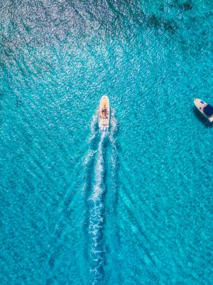 Yachts at the sea in Balearic islands, Spain. Aerial view of luxury floating boat in transparent blue water at sunny day. Summer landscape. Top view from drone. Seascape with motorboat in bay. Travel